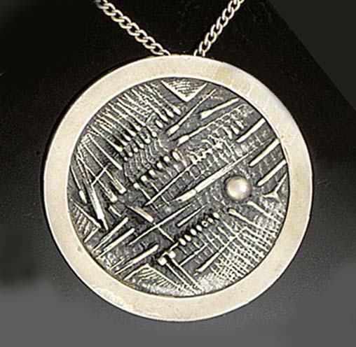 A pendant by Arnaldo Pomodoro,