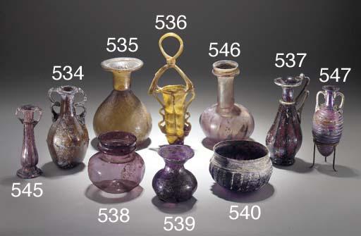 A ROMAN DARK AMBER GLASS FLASK