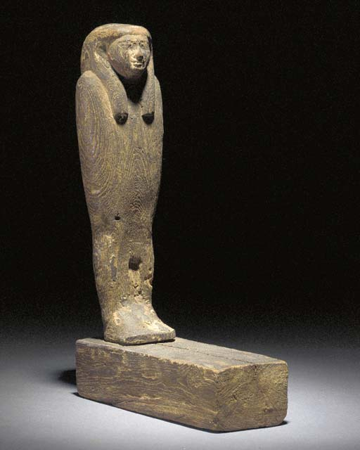 AN EGYPTIAN WOODEN FIGURE OF P