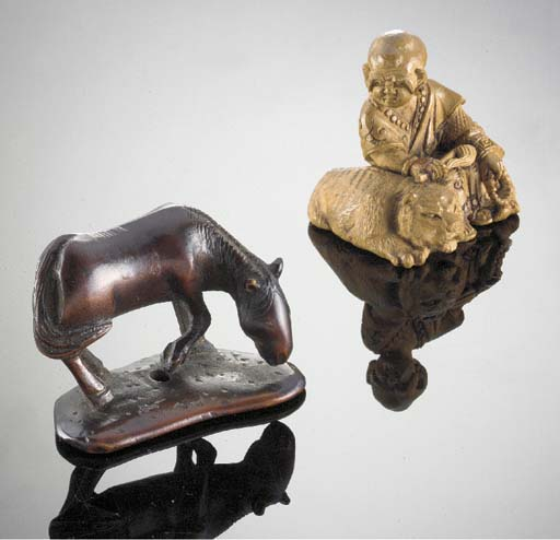 A wood netsuke of a grazing ho