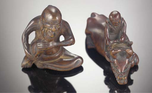 A wood netsuke of a boy seated