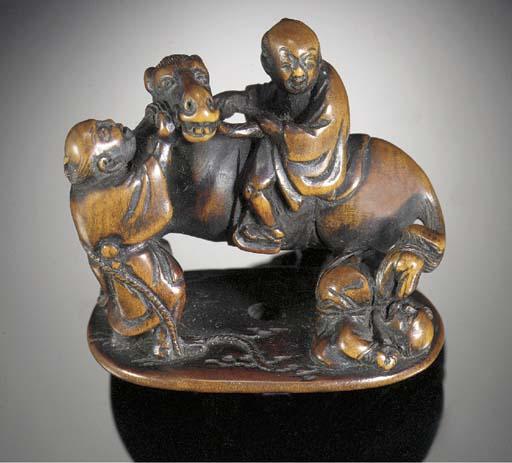 A wood netsuke of three figure