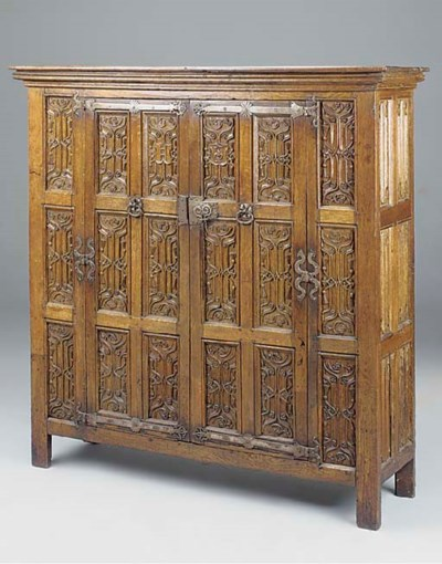 A CARVED OAK PANELLED CUPBOARD