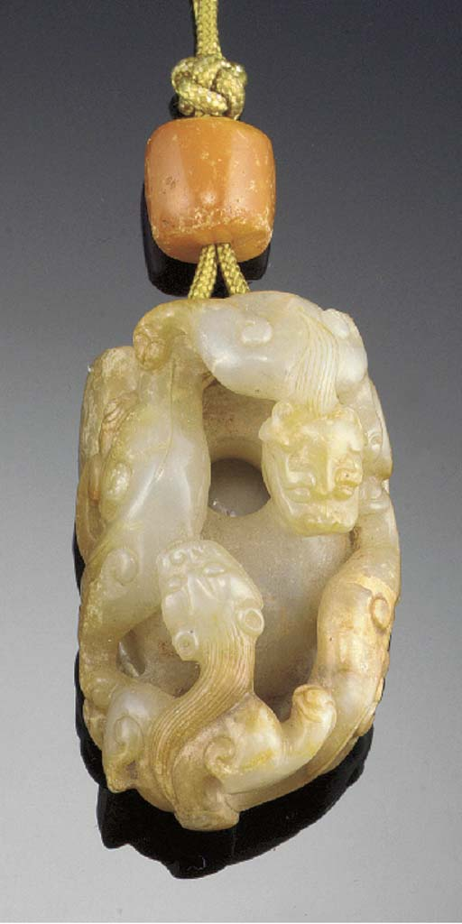 A mottled jade pendant carved