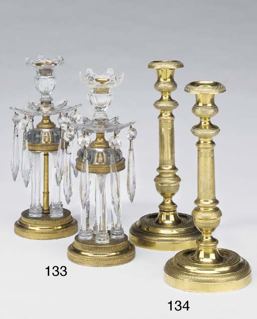 A pair of Victorian or Edwardian gilt metal and cut glass mounted candlesticks, circa 1900