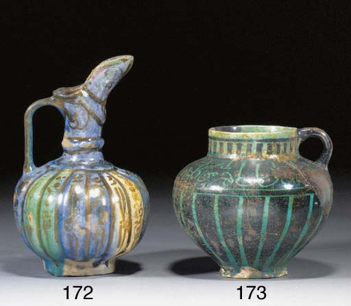 A Kashan turquoise and dark blue glazed globular pottery ewer 12th century