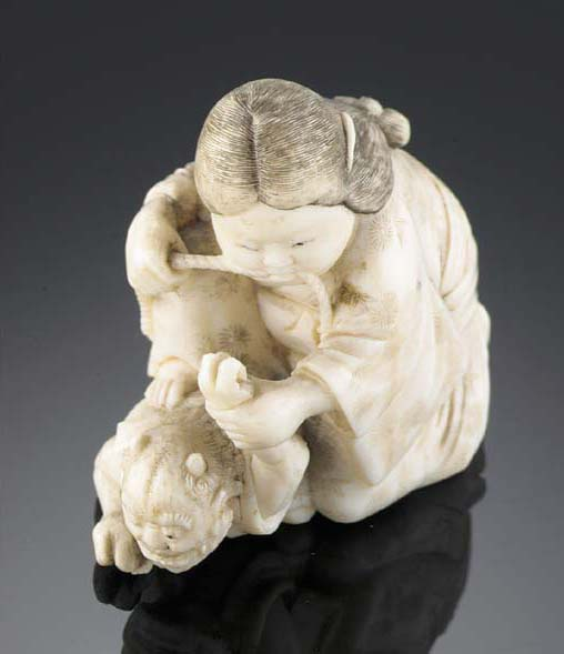 An ivory netsuke of Okami with