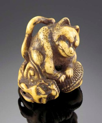 A stag-antler netsuke of a dog