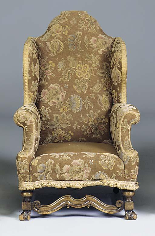 A walnut wing armchair, first