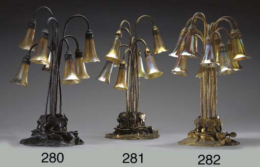 A TWELVE-LIGHT LILY IRIDESCENT GLASS AND GILT-BRONZE TABLE LAMP