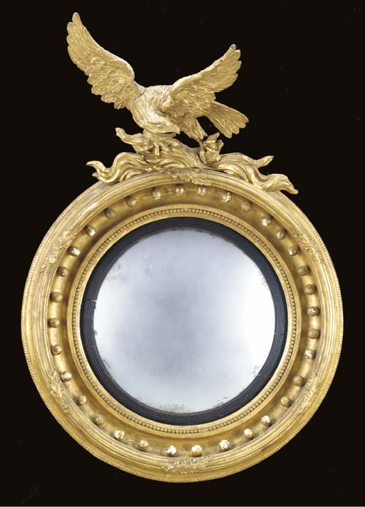 A CLASSICAL CARVED AND GILDED CONVEX MIRROR