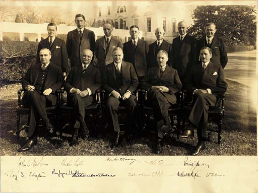 """HOOVER, Herbert. Photograph signed (""""Herbert Hoover"""") as President, also signed by Vice President Charles Curtis and eight members of his Cabinet; Secretary of the Interior Roy Lyman Wilbur, Attorney General William D. Mitchell, Postmaster General Walter F. Brown, Secretary of Agriculture Arthur M. Hyde, Secretary of the Treasury Ogden L. Mills, Secretary of State Henry L. Stimson, Secretary of War Patrick J. Jurley and Secretary of the Navy Charles F. Adams, n.p., n.d. [ca. 1932]. 14 3/16 x 19 in., sepia toned, photograph by Schutz (marked on photo and back), two creases and minor damage at upper edge, minor soiling, upper left corner strengthened on verso."""