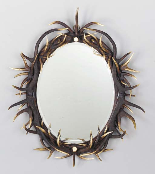 AN OVAL HORN-MOUNTED MIRROR,