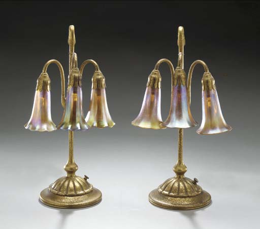 A PAIR OF THREE LIGHT 'LILY' FAVRILE GLASS AND GILT-BRONZE