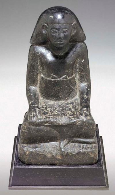 AN EGYPTIAN BASALT FIGURE OF A