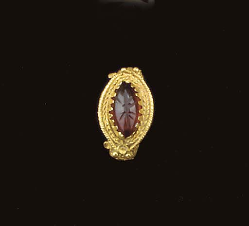A GREEK GOLD AND GARNET FINGER