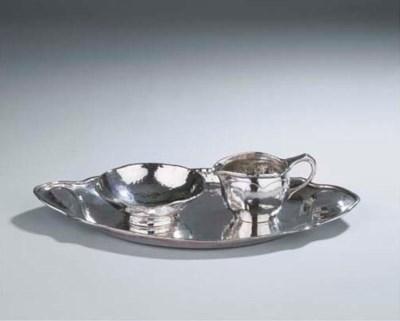 A Dutch hammered silver cream