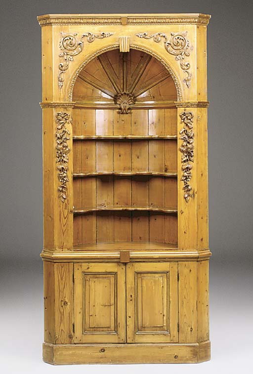 A carved pine corner cupboard,