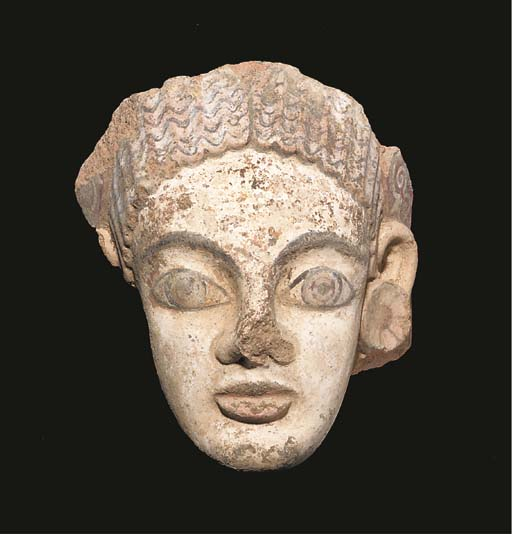 AN ETRUSCAN PAINTED TERRACOTTA ANTEFIX WITH FEMALE HEAD