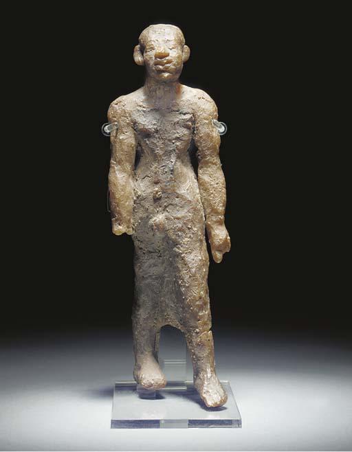 AN EGYPTIAN WAX FIGURE OF A STRIDING MALE FIGURE