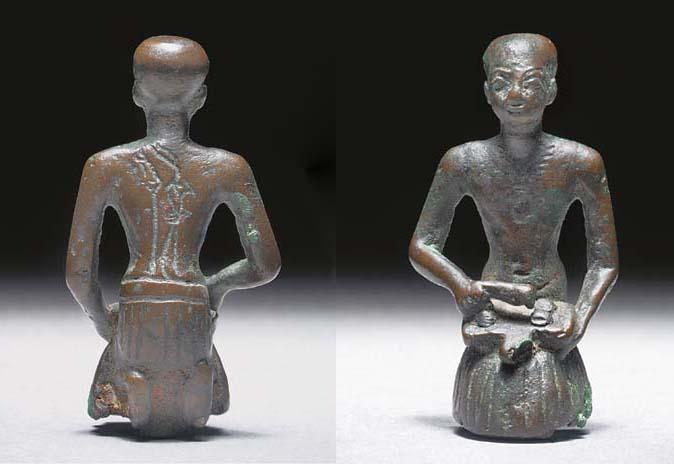 AN EGYPTIAN BRONZE FIGURE OF A KNEELING LIBATION PRIEST