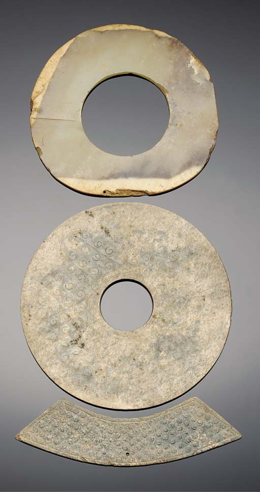 A partially calcified mottled green jade bi disc, Neolithic and later