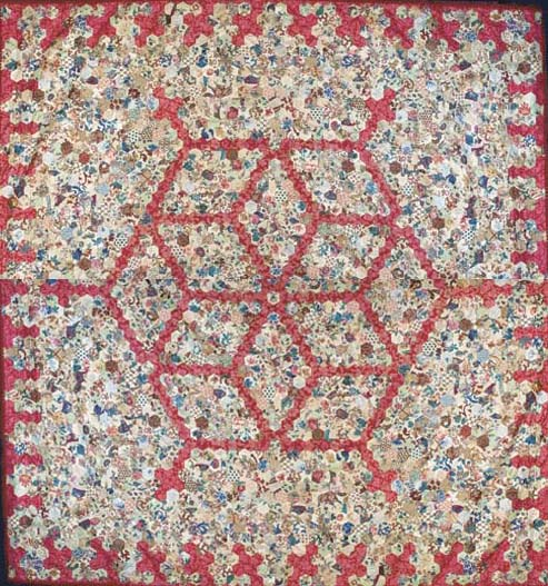 A patchwork coverlet, pieced with a diamond design from hexagons of bright polychrome chintz against a red ground--90 x 84in. (229 x 213.5cm.), circa 1860s with some earlier fabrics, backed in printed cotton, trimmed in later red braid