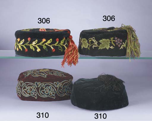 A cap, the purple and ivory ground embroidered overall in floss silks and gold metal thread with figures, flowers, a bird and decorative roundels, Indian, early 20th century; a smoking cap of charcoal velvet, embroidered in coloured wools with naturalistic roses, with pink and green tassel, circa 1870s; and two further velvet smoking caps