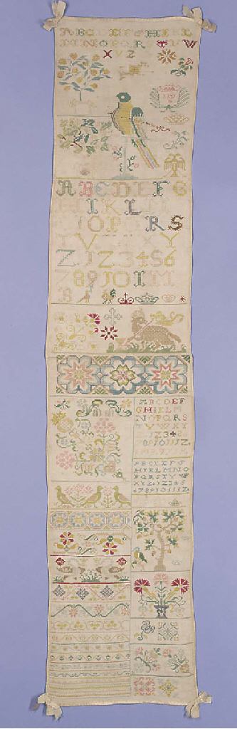 A band sampler, worked in coloured silks with alphabets and numerals, trees, birds and flowers, the uppers section with a central design of a parrot--42½ x 8¾in. (108 x 22cm.), probably German, very slightly worn