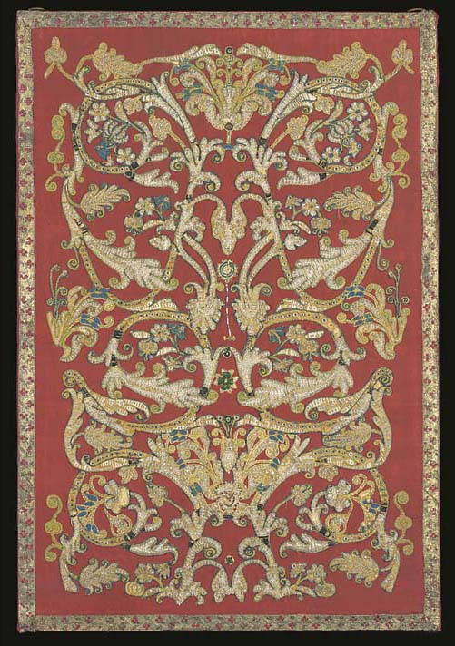 A re-applied beadwork panel, appliquéd in pale yellow ribbed silk and embroidered in glass beads with scrolling foliate stems bearing white feathery leaves and blue and white flowers against a crimson silk ground--39¾ x 27in. (101 x 68.5cm.), Italian, 17th century, some wear, mounted on a stretcher