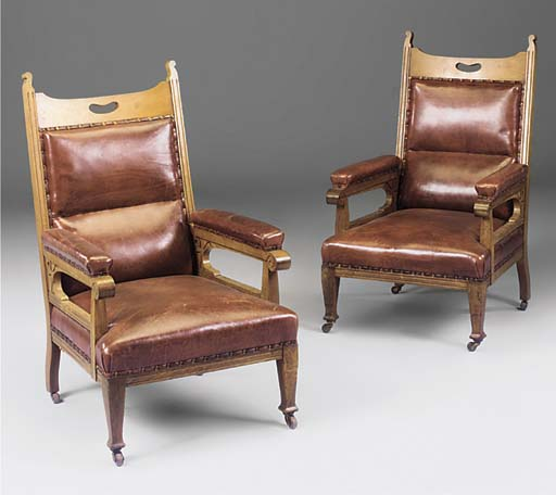 A PAIR OF OAK AND RED LEATHER UPHOLSTERED EASY ARMCHAIRS