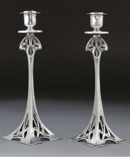 A PAIR OF SILVERED METAL CANDL