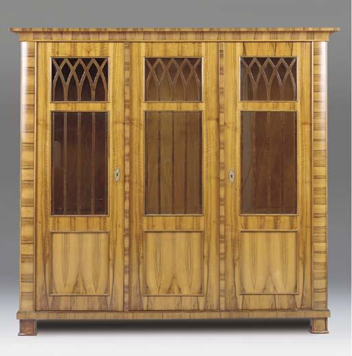 A WALNUT VENEERED THREE DOOR DISPLAY CABINET