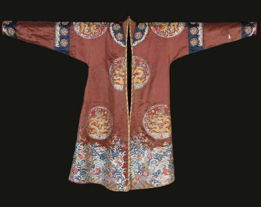 An altered long gua robe of chestnut brown satin, embroidered in silks and couched gilt thread with eight dragon roundels, with a turbulent sea-wave border below, the borders of midnight blue satin embroidered with small dragon roundels, 19th century, re-tailored probably in the 20th century, sleeves and neckline altered, brocade facings added, some stains