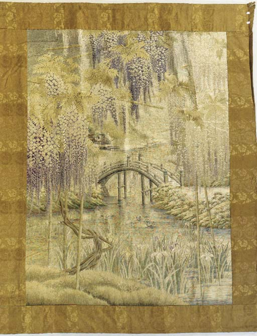 An embroidered hanging, worked in floss silks with trailing wysteria blossom framing a riverside view, with a wooden bridge, with bamboo and irises growing by the water's edge, trimmed with brocade borders--92 x 72½in. (234 x 184cm.), circa 1900