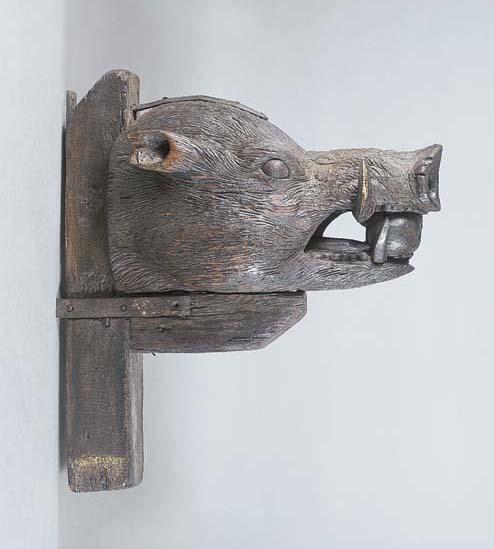 A LARGE CARVED OAK BOAR'S HEAD