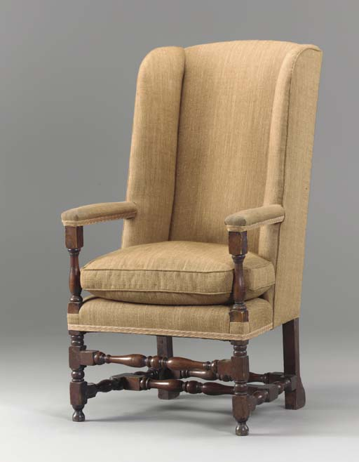 AN OAK CONTINENTAL STYLE WING ARMCHAIR,