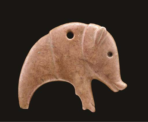 A SYRIAN RED MARBLE AMULET