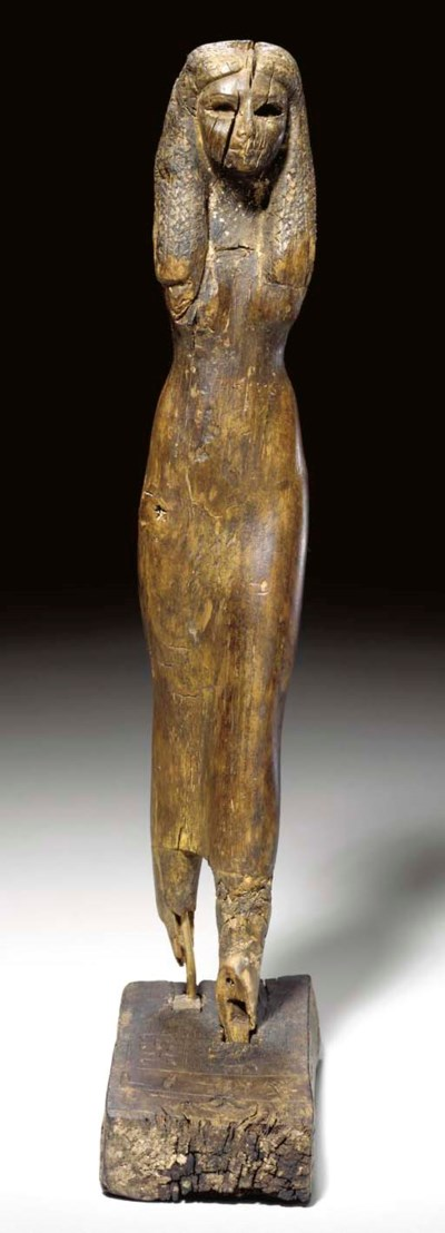 AN EGYPTIAN WOOD FIGURE OF THE