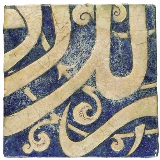 A KASHAN COBALT BLUE, BLACK AND WHITE MOULDED INSCRIPTION TILE