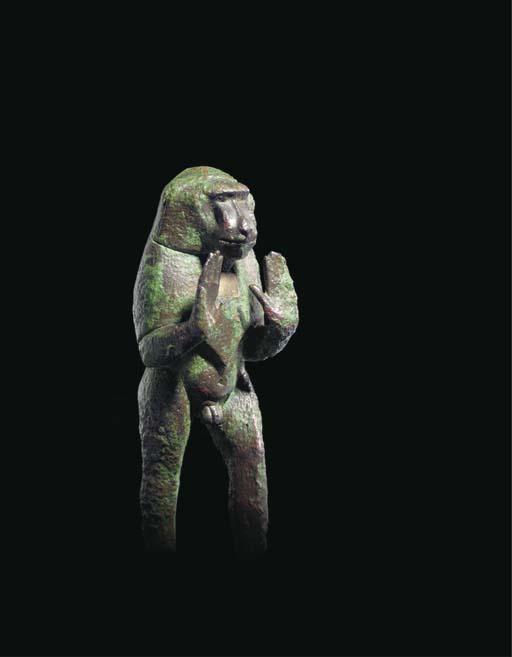 AN EGYPTIAN BRONZE FIGURE OF A