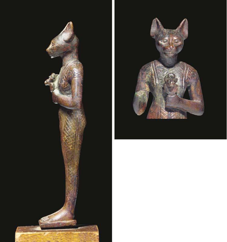 AN EGYPTIAN BRONZE STATUE OF B