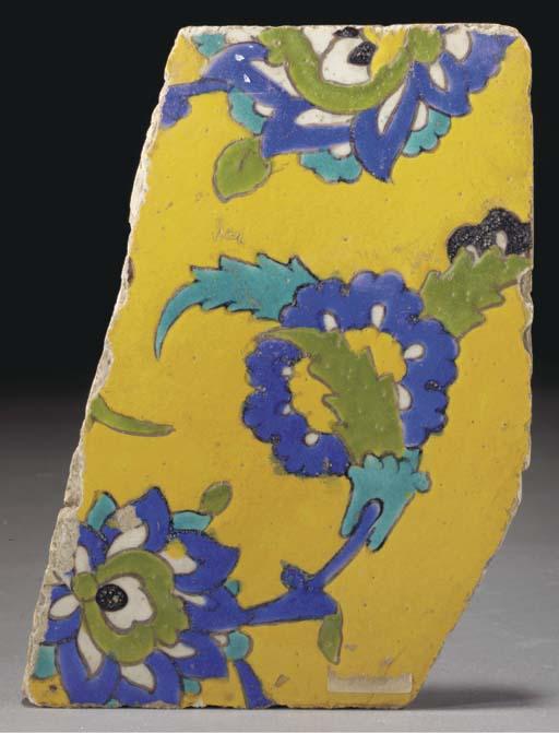 A fragmentary Isfahan Cuerda Seca pottery tile, Iran, 17th century