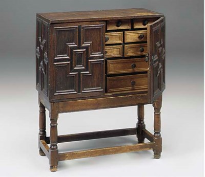 AN ENGLISH OAK CABINET ON STAN