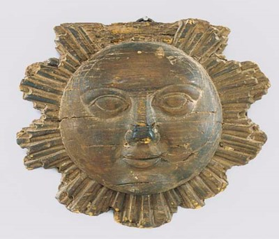A CARVED PINE MASK OF THE SUN