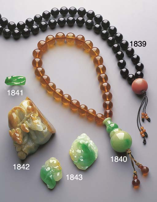 A STRAND OF AMBER BEADS AND A