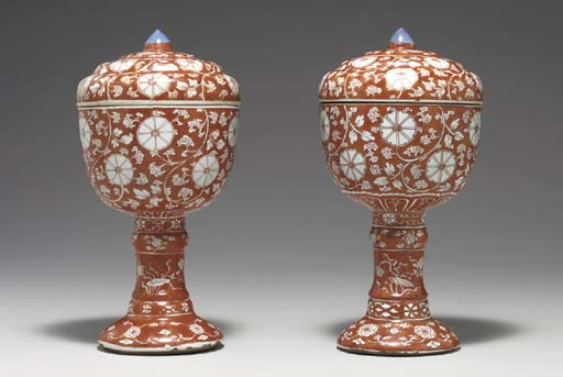 A PAIR OF IRON-RED PEDESTAL BO