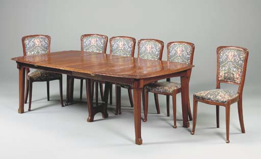 A CARVED MAHOGANY DINING SUITE