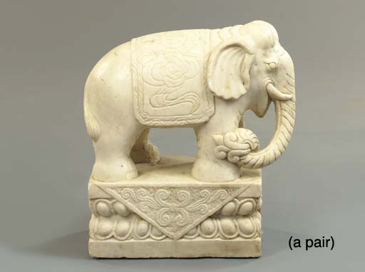 A PAIR OF CARVED WHITE MARBLE FIGURES OF ELEPHANTS TOGETHER WITH A PATINATED METAL PUTTO HOLDING SUNDIAL