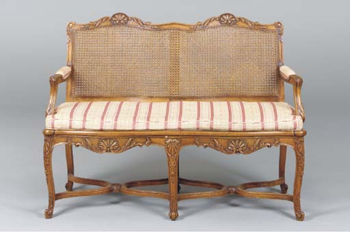 A PROVINCIAL LOUIS XV STYLE CARVED WALNUT AND CANED SETTEE,